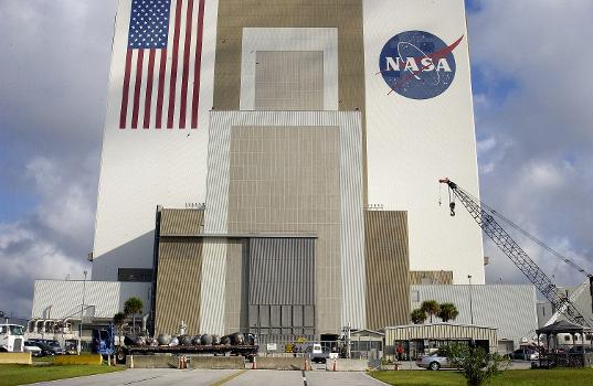 A flatbed truck carrying pieces of debris of Space Shuttle Columbia arrives outside the Vehicle Assembly Building (VAB). The debris is being transferred from the Columbia Debris Hangar to the VAB for permanent storage. More than 83,000 pieces of debris were shipped to KSC during search and recovery efforts in East Texas. That represents about 38 percent of the dry weight of Columbia, equaling almost 85,000 pounds.  Source: NASA  Photo Number: KSC-03PD-2614