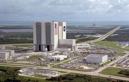 Vehicle Assembly Building (VAB) : An aerial view of the Launch Complex 39 area shows the Vehicle Assembly Building (center), with the Launch Control Center on its right. On the west side (lower end) are (left to right) the Orbiter Processing Facility, Process Control Center and Operations Support Building. Looking east (upper end) are Launch Pads 39A (right) and 39B (just above the VAB). The crawlerway stretches between the VAB and the launch pads toward the Atlantic Ocean, seen beyond them. At right is the turning basin where new external tanks are brought via ship.