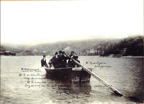 Pont de Pyrimont : L'équipe du chantier sur la barque du bac de SURJOUX. Sont présents sur le bateau: à gauche: M. VILLEMAGNE, conducteur des Ponts et Chaussées, M. S. de MOLLINS, Ingénieur Lausanne, M. SCHOENDOERFER, Ingénieur en chef des Ponts et Chaussées, M. DUVAL; ingénieur des Ponts et Chaussées. À droite: M. GRANDJEAN, entrepreneur, M. CHANAY, contremaître