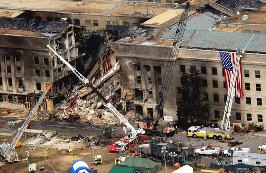 An aerial view, two days later, of the impact point on the Pentagon where the hijacked American Airlines Flight 77, a Boeing 757-200 entered, breaking up in the process. Shortly after 8 AM on September 11, 2001 in an attempt to frighten the American people, five members of Al-Qaida, a group of fundamentalist Islamic Muslims, hijacked Flight 77 from Dulles International Airport just outside Washington DC. About 9:30 AM they flew the aircraft and 64 passengers into the side of the Pentagon. The impact destroyed or damaged four of the five «rings,» in that section, that circle the building. That section of the Pentagon was in the finishing stages of a renovation program to re-enforce and update the building. Fire fighters fought the fire throughout the night. The Pentagon attack followed a similar attack, two hijacked passenger planes flown into the twin towers of the New York World Trade Center, on the same day, in what is being called the worst terrorist attack in history. The huge American flag visible to the right of the damaged area is a garrison flag sent from the US Army Band at nearby Fort Myer, Virginia. It is the largest authorized (20 x 38) flag for the military. 3rd Infantry soldiers and fire fighters unfurled the flag over the side. Each night floodlights illuminated it. Search and rescue operations continue looking for survivors and casualties