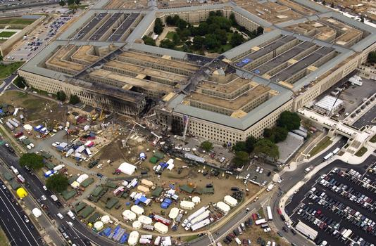 An overall aerial view, two days later, of the impact point on the Pentagon where the hijacked American Airlines Flight 77, a Boeing 757-200 entered, breaking up in the process. Shortly after 8 AM on September 11, 2001 in an attempt to frighten the American people, five members of Al-Qaida, a group of fundamentalist Islamic Muslims, hijacked Flight 77 from Dulles International Airport just outside Washington DC. About 9:30 AM they flew the aircraft and 64 passengers into the side of the Pentagon. The impact destroyed or damaged four of the five «rings,» in that section, that circle the building. That section of the Pentagon was in the finishing stages of a renovation program to re-enforce and update the building. Fire fighters fought the fire throughout the night. The Pentagon attack followed a similar attack, two hijacked passenger planes flown into the twin towers of the New York World Trade Center, on the same day, in what is being called the worst terrorist attack in history. The huge American flag visible to the right of the damaged area is a garrison flag sent from the US Army Band at nearby Fort Myer, Virginia. It is the largest authorized (20 x 38) flag for the military. 3rd Infantry soldiers and fire fighters unfurled the flag over the side. Each night floodlights illuminated it. Search and rescue operations continue looking for survivors and casualties