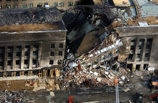 An aerial view of the destruction at the Pentagon caused by a terrorist attack. The morning of September 11th, in an attempt to frighten the American people, five members of Al-Qaida, a terrorist group of fundamentalist Muslims, hijacked American Airlines Flight 77, then deliberately impacted the Pentagon killing all 64 passengers onboard and 125 people on the ground. The impact destroyed or damaged four of the five rings in that section of the building. Firefighters fought the fire through the night. The Pentagon was the third target by four hijacked aircraft, the twin towers of the World Trade Center (WTC) were the other targets, and one unknown when the passengers brought the aircraft down in a Pennsylvania field