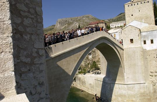Old Mostar Bridge after reconstruction : Local citizens walk over the Old Bridge (Stari Most) for the first time during the grand opening ceremony celebrating the re-opening of this bridge in Mostar, Herzegovina-Neretva Canton, Bosnia-Herzegovina (BIH). This bridge is the symbol of Mostar and was destroyed during the 1993 Balkan War