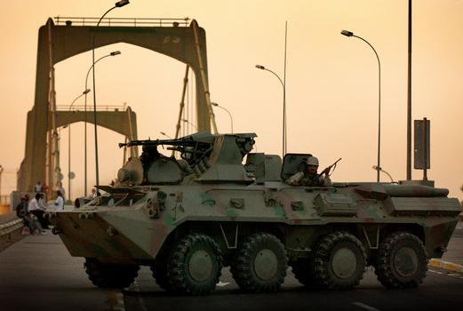 In the early morning hours, Iraqi National Guard (ING) troops move a BTR-80A (8X8) Armored Personnel Carrier (APC) into position on the 14th of July bridge in Baghdad, Iraq (IRQ), to provide security for the Iraqi Democratic National Conference during Operation IRAQI FREEDOM