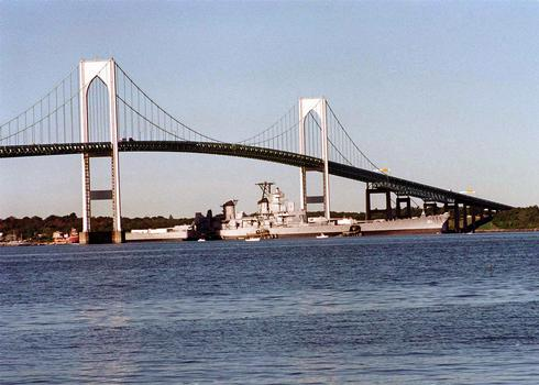 The decommissioned battleship Iowa (BB 61) passes under the Newport Bridge on its way to join the decommissioned aircraft carriers Forrestal and Saratoga at the Naval Education and Training Center, Rhode Island. The three deep draft ships were moved by the US Navy from Philadelphia as a result of the Base Realignment and Closure (BRAC) decision to close the former Philadelphia Naval Shipyard