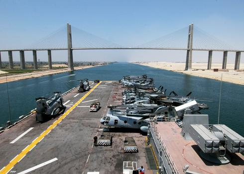 The US Navy (USN) Wasp Class Amphibious Assault Ship USS IWO JIMA (LHD 7) prepares to pass underneath the Mubarak Peace Bridge (in the background) as it transits through the Suez Canal, Egypt