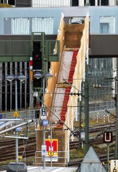 Die Treppen vom Arnulfsteg zu den Bahnsteigen noch mit Holz verschalt:Aufnahme von außerhalb des Bahngeländes.