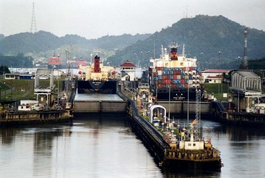 Panama Canal Miraflores Locks, looking northwards, towards Miraflores Lake, with the Pedro Miguel locks visible in the background. In the foreground, on the end of the approach wall, a large illuminated arrow can be seen; this rotates to indicate to ships which chamber they are to enter
