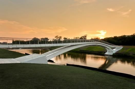 A new pedestrian footbridge, designed by Boston Architectural Firm - Rosales + Partners was dedicated in Forth Worth, Texas. The first bridge of its kind in North America, the $3-million Phyllis J. Tilley Memorial Bridge features a 163 ft steel deck arch topped with a stress ribbon—two structural systems that are not typically combined