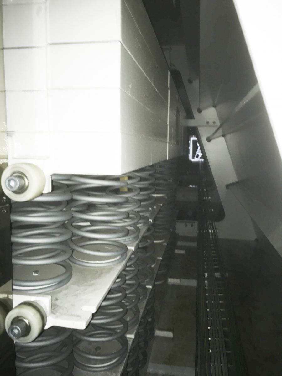 Nouveau toit pour le stade Roland Garros Vue sur la «profondeur» - c'est-à-dire la longueur - des poutres du toit. En haut de l'image la masse vibrante allongée, en bas les paquets de ressorts qui ont été ajustés individuellement aux fréquences des poutres. L'inclinaison à droite résulte de la géométrie des poutres caissons en acier. La lumière au centre montre l'entrée suivante.