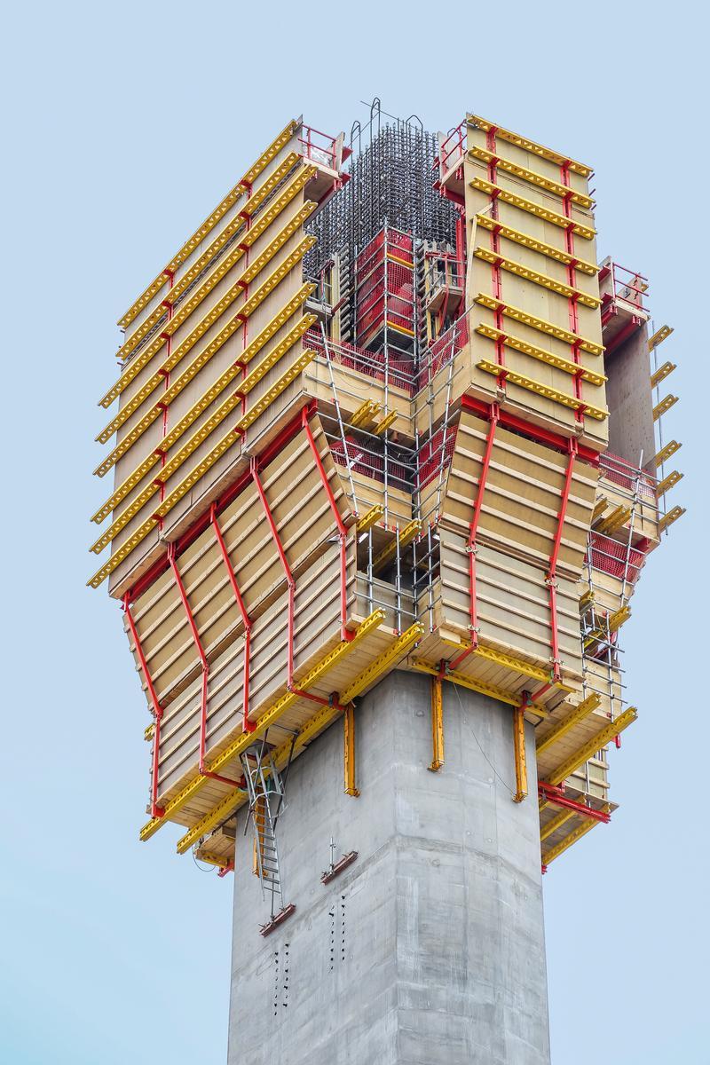 Mediendatei Nr. 272781 Als Außenschalung für den oberen Schaft wurde das Selbstklettersystem ACS R mit der VARIO GT 24 Träger-Wandschalung eingesetzt; die Wandschalung wurde dabei von der oberen Arbeitsplattform abgehängt. Dank dieser Sonderkonstruktion ließ sich die Schalung zurückfahren und die Arbeitsbühne nach oben klappen. Anschließend konnten Material und PERI UP Flex Bewehrungsgerüste per Kran von oben eingebracht werden.