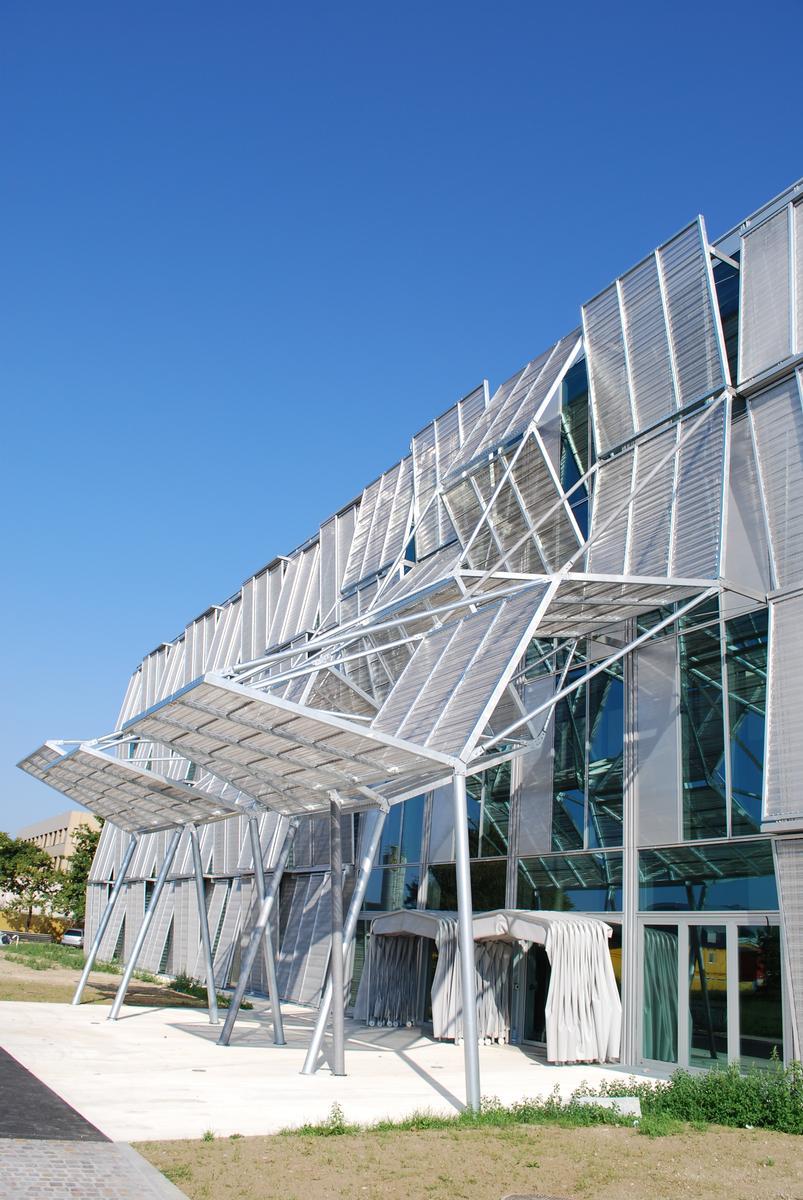 Mediendatei Nr. 242917 Die abwechselnd oben und unten ausgestellten Paneele bestehen aus naturfarben eloxiertem Aluminiumgewebe – im Eingangsbereich aus Edelstahlgewebe – vom Typ Escale der GKD.