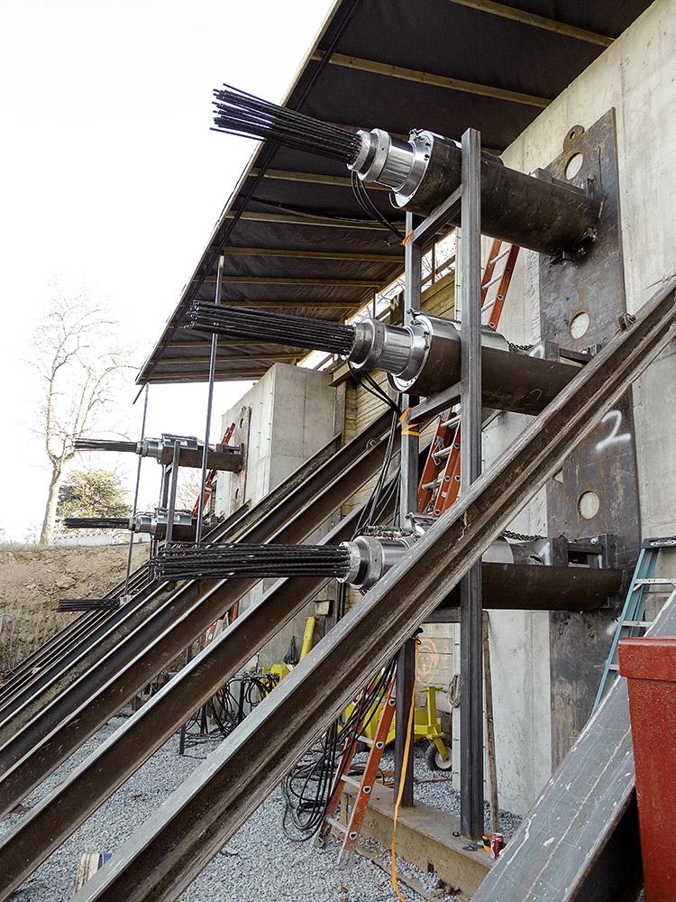 Mediendatei Nr. 268260 Die Spannglieder waren auf der einen Seite an den Tunnelkästen montiert und wurden auf der anderen Seite des Bahndamms mit Spannpressen an einer temporären Stützwand fixiert.