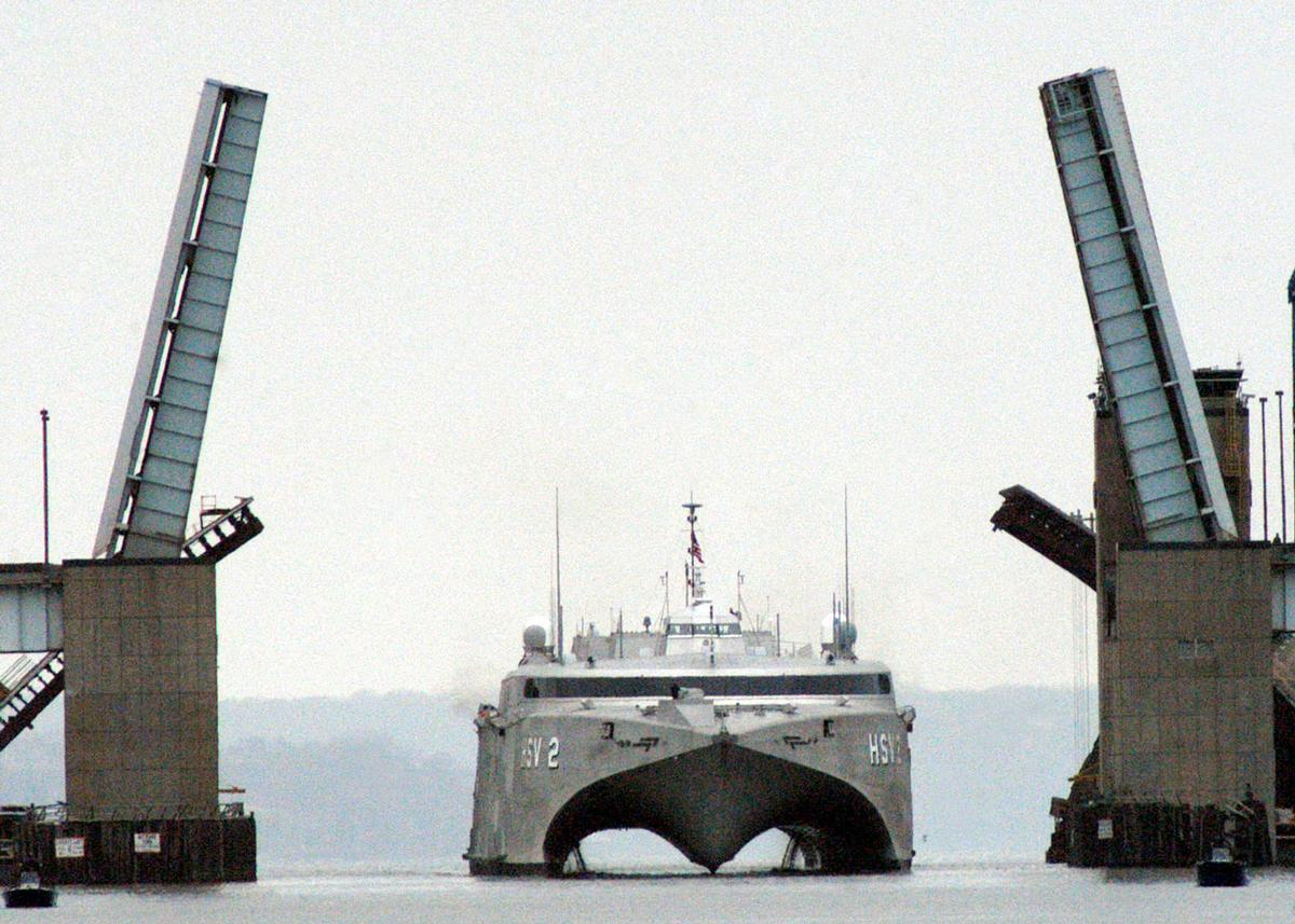 The Woodrow Wilson Bridge lifts opens to let the High Speed Vessel 2 (HSV-2) SWIFT pass as the experimental ship glides across the Potomac River. SWIFT will port in Old Town Alexandria, Virginia, where the crew will enjoy liberty and show off the ship to the public and media.